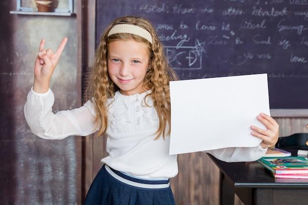 L'école est un endroit heureux petit enfant heureux tenant du papier blanc sur fond de tableau noir petite fille h...