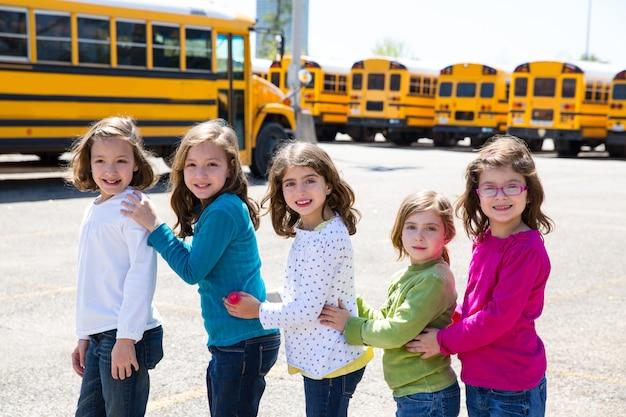 École filles amis dans une rangée à pied de bus scolaire