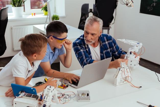 À l'école. joyeux garçons intelligents parlant à leur professeur tout en ayant un cours de sciences