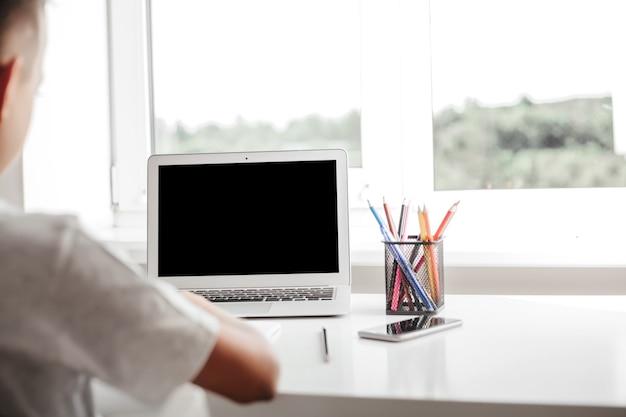 École à la maison grâce à l'enseignement à domicile en ligne. l'enfant est assis devant l'ordinateur