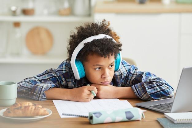 Écolier africain dans les écouteurs assis à la table et regarder la leçon en ligne sur ordinateur portable, il étudie en ligne