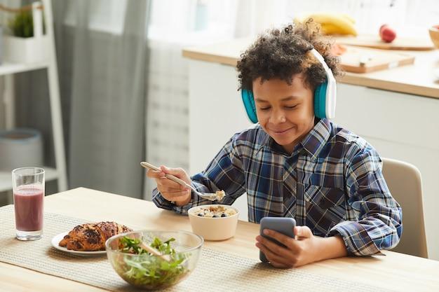 Écolier africain portant des écouteurs à regarder des cours en ligne sur son téléphone portable et prendre son petit déjeuner