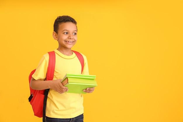 Écolier afro-américain mignon avec des livres sur l'orange