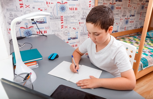 Écolier à l'aide d'un ordinateur de bureau pour l'étude en ligne homeschooling
