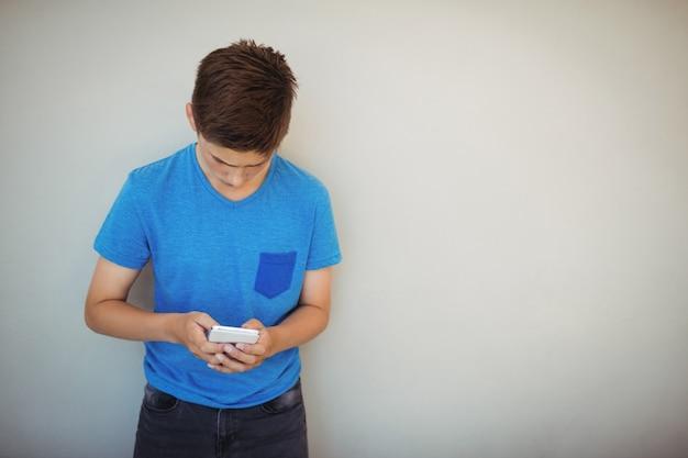Écolier à l'aide de téléphone portable dans le couloir à l'école
