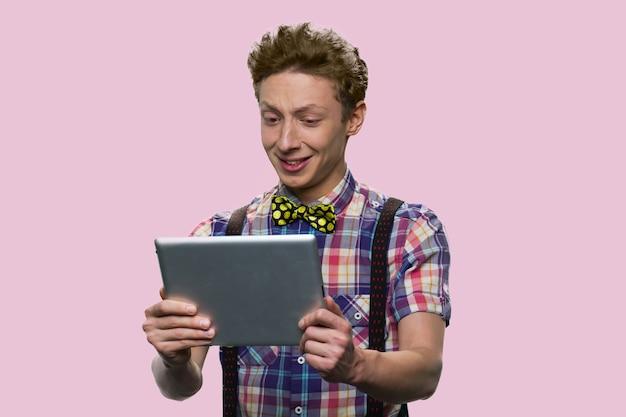 L'écolier américain tient une tablette. beau garçon regarde la tablette. isolé sur fond rose.