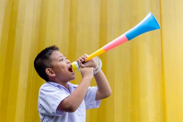 Écolier asiatique soufflant une corne colorée sur fond jaune.