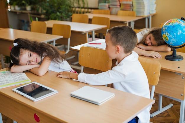 Écolier assis dans la salle de classe avec des écolières endormies