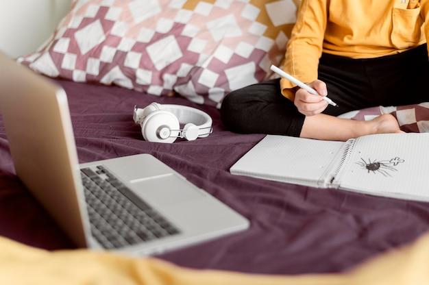 Écolier assis dans son lit dans sa chambre