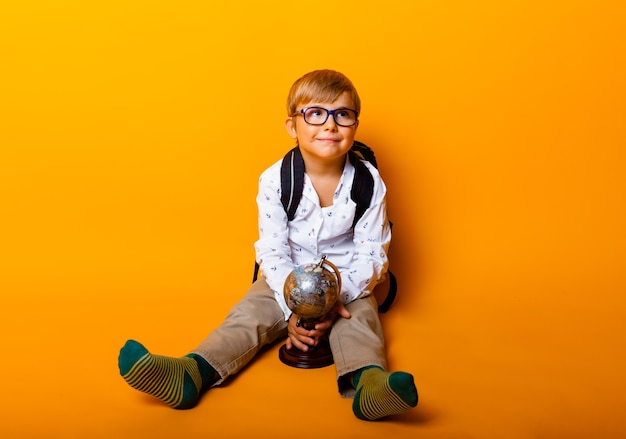 Un écolier assis dans des verres détient un globe terrestre isolé sur fond jaune