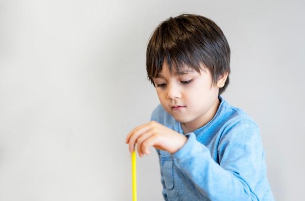 Écolier assis seul à jouer avec un crayon avec un visage ennuyé