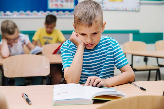 Écolier, assis, table, lecture, manuel