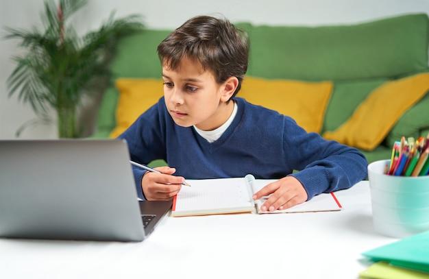 Écolier ayant des cours en ligne assis à la maison en quarantaine, utilisant un ordinateur portable et prenant des notes