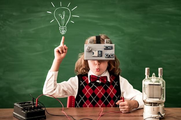 Écolier avec casque de réalité virtuelle en classe enfant heureux contre le concept d'idée de tableau vert
