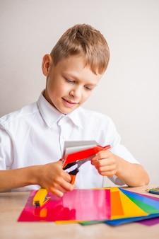 Un écolier en chemise blanche coupe un homme dans du papier rouge avec des ciseaux orange