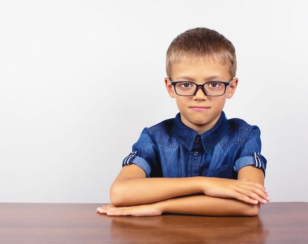 Écolier en chemise bleue assis à la table. garçon avec des lunettes