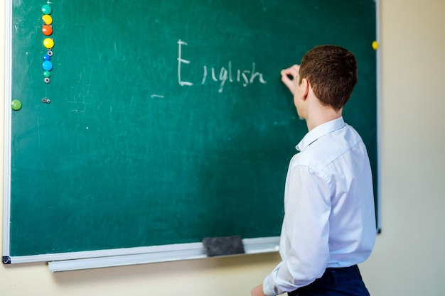 Écolier en chemise légère wrting mots anglais sur tableau noir. retour au concept de l'école.