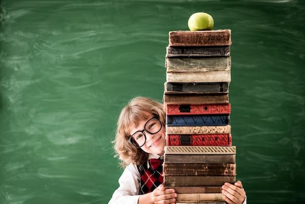 Écolier en classe. heureux enfant tenant des livres contre le tableau vert. notion d'éducation