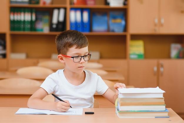 Écolier concentré assis au bureau et écrivant dans un cahier avec un camarade de classe assis derrière