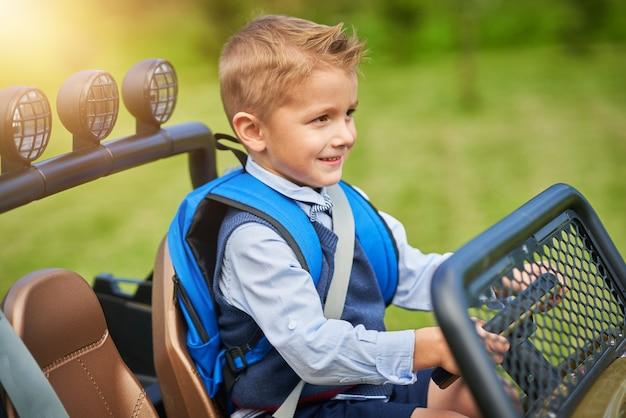 Écolier conduisant une voiture pour enfants avec sac à dos