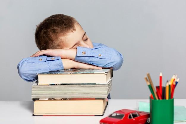 Un écolier dans une chemise bleue dort sur une pile de livres à la table.