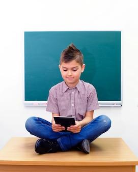 Écolier, dans, lotus pose, regarder ordinateur tablette