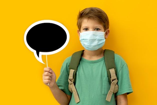 Écolier dans un masque médical avec un sac à dos. retour à l'école.