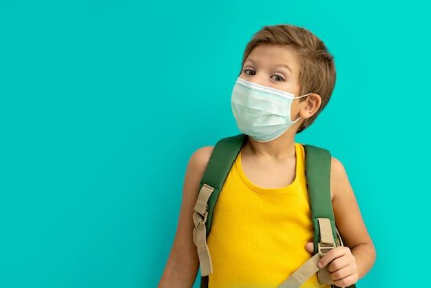 Écolier dans un masque médical avec un sac à dos.
