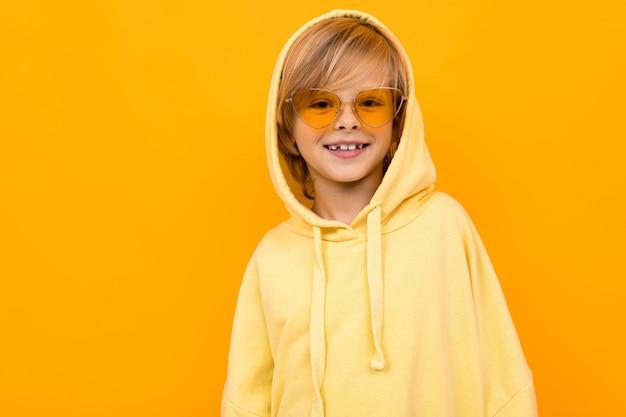 Écolier dans un sweat à capuche jaune sur fond jaune