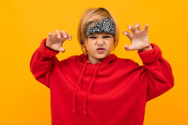 Écolier dans un sweat à capuche rouge et un bandana grogne à la caméra