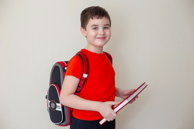 Écolier dans un t-shirt rouge avec une sacoche