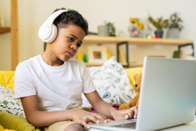 Écolier diligent de l'âge élémentaire dans les écouteurs en appuyant sur les boutons du clavier d'ordinateur portable tout en étudiant par table dans l'environnement familial