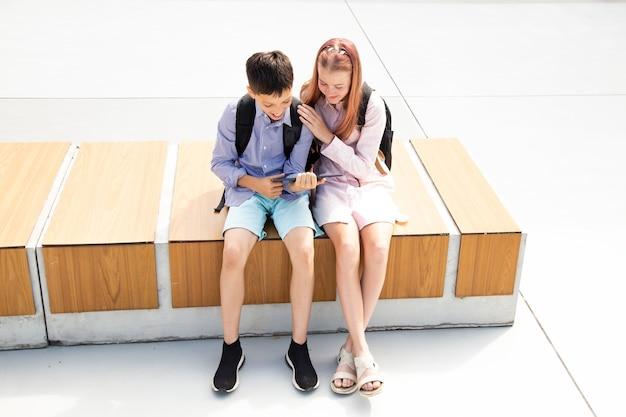 Écolier écolière adolescents rire s'amuser après les cours assis sur un banc en bois dans la cour d'école, tablette d'utilisation de fond en béton, concept d'éducation en ligne, technologies modernes dans la vie des enfants