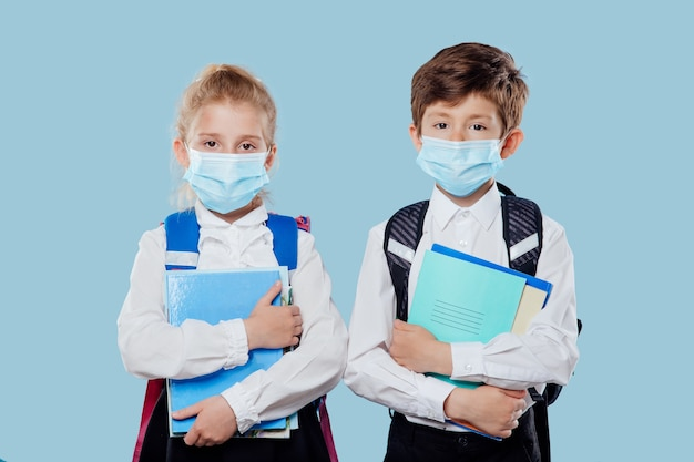 L'écolier et l'écolière avec masque médical et sac à dos ont des cahiers et des livres à la main isolés sur ...