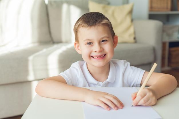 Écolier écrit sur un papier à la maison.