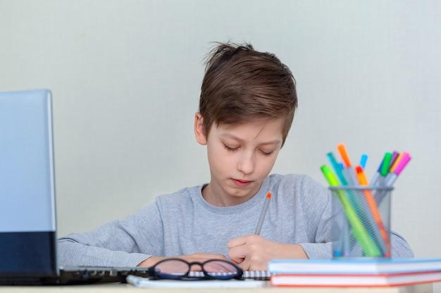 L'écolier écrit ses devoirs avec sa main gauche.