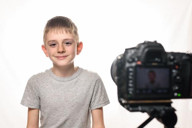 L'écolier est prêt à donner l'interview sur un caméscope.