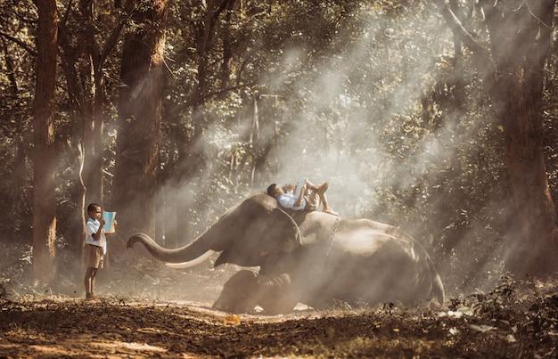 Écolier étudiant dans la jungle avec son ami éléphant