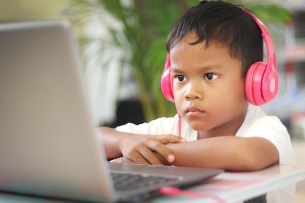 Un écolier étudie en ligne sur un ordinateur portable à la maison. communique en ligne avec un enseignant. enseigne des leçons de l'école à l'ordinateur. participe à l'enseignement à distance.