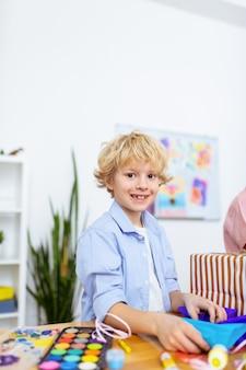 Écolier excité. écolier blond aux yeux noirs se sentant excité après une belle leçon d'art et faisant des décorations