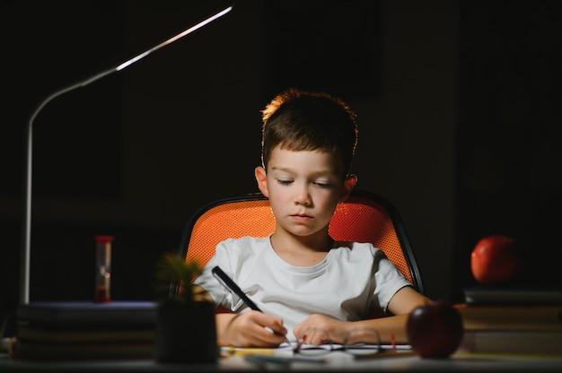 Écolier faisant ses devoirs à table dans sa chambre.