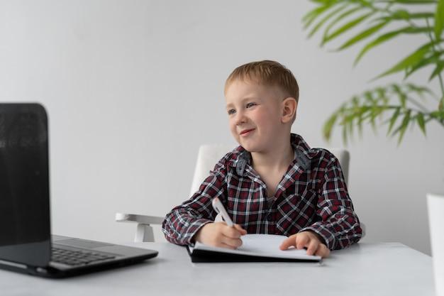 Un écolier fait ses devoirs de quarantaine à la maison