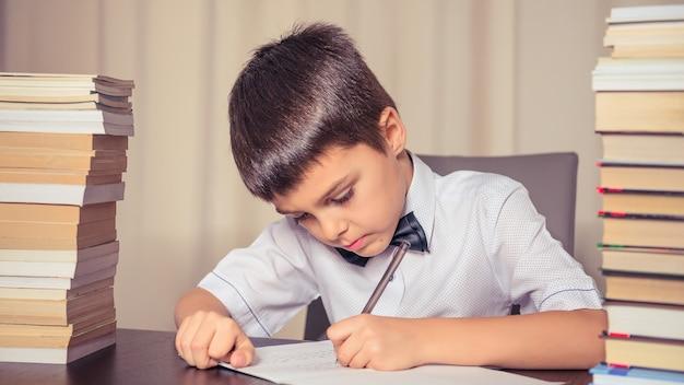 L'écolier fait ses devoirs à la table, à côté de deux piles de livres.