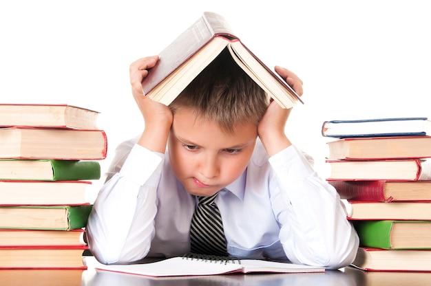 Un écolier fatigué et à la traîne est assis dans une bibliothèque avec des livres et apprend des leçons. refus d'apprendre.