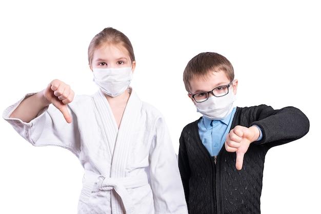 Écolier garçon et fille athlète montrent les pouces vers le bas. masqué. isolé sur fond blanc. photo de haute qualité