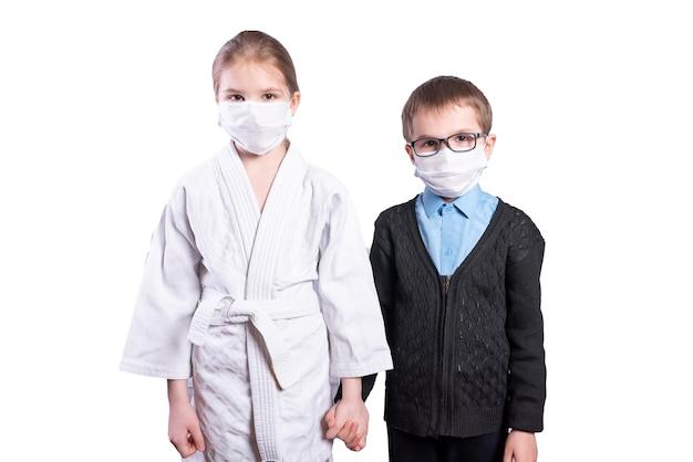 Écolier garçon et fille athlète se tiennent la main. masqué. isolé sur fond blanc. photo de haute qualité