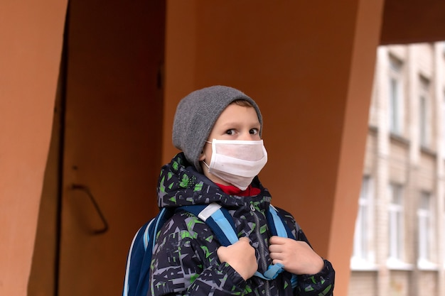 Écolier garçon sort de l'école avec un masque de protection