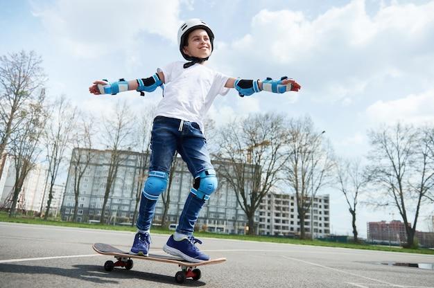 Un écolier heureux et souriant dans un équipement de protection et un casque garde l'équilibre tout en faisant du skateboard