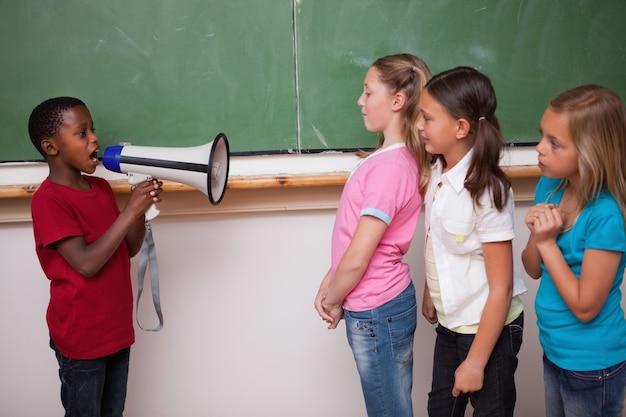 Écolier hurlant à travers un mégaphone à ses camarades de classe