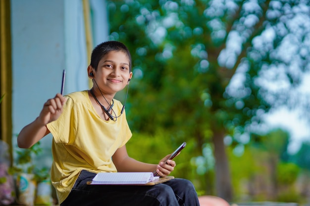 Écolier indien tenant un cours d'apprentissage à distance par téléphone à l'aide d'une application mobile, regardant une leçon en ligne, appel vidéo dans l'application prenant des notes en étudiant à la maison
